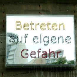 """Schild """"Betreten auf eigene Gefahr"""" im Plattenbaumuseum Betonzeitschiene."""