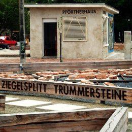 Das Pförtnerhaus im Plattenbaumuseum Betonzeitschiene. Im Vordegrund liegen Ziegelsplitt und Trümmersteine.