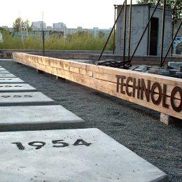 Ausschnitt des Plasttenbaumuseums Betonzeitschiene in Dresden. Langer Holzbalken mit der Aufschrift Technologie und Bodenplatten mit Jahreszahlen.