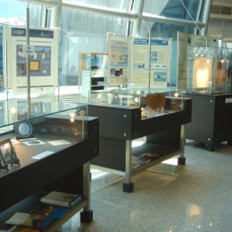 Mehrere Ausstellungsstücke für das Nano-Museum Dresden, schwarze Ausstellungstische mit Glasvitrinen