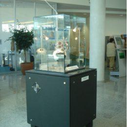Quadratisches Ausstellungsobjekt in schwarz mit einer Glasbox mit einem Fußball