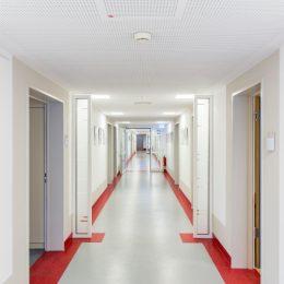 Ansicht des gesamten Flures im Universitätsklinikum Dresden. Gestaltung der Station mit weißen Ränden und einem roten Übergang zwischen Boden und Wand.