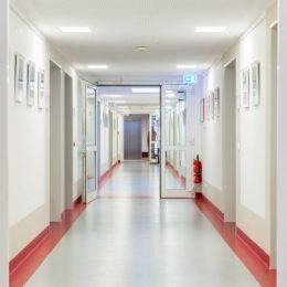 Flurbereich einer Krankenstation im UIniversitätskrankenhaus Dresden. Weißer Flur mit roten Gestaltungselementen.