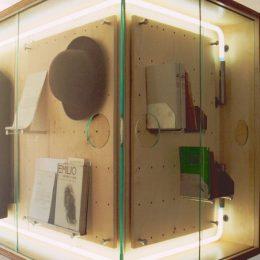 Eine beleuchtete Vitrine mit Hut und Büchern im Erich Kästner Museum