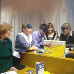 Travelling Micromuseum Exhibition in Omsk, Besucher unterhalten sich an einem gelben Ausstellungsobjekt