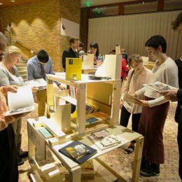 Travelling Micromuseum Exhibition in Washington, Besucher lesen Bücher an einem Ausstellungsobjekt