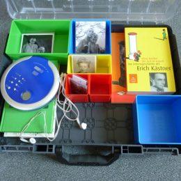 Elemente des Erick Kästner Museumsmobils,ein Koffer mit bunten Schalen, Fotos,Büchern und einem CD-Player