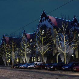 Fassadenbeleuchtung des Universitätsklinikums Dresden und beleuchtete Bäume vor dem Gebäude.