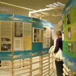 Zahlreiche Besucherinformationen an Holzelementen angebracht, blau-weiße Poster
