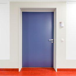 Flur im Universitätsklinikum Dresden, blaue Tür mit roter Fußleiste