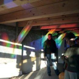 Besucher im Stadtspeicher Jena schauen von innen nach außen durch die Hologrammfassade. An der Wand und der Decke ist das einfallende Licht in seine Spektralfarben zerteilt.