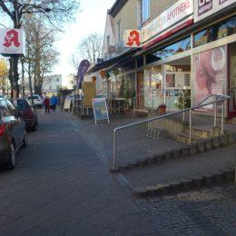 Der Fußgängerweg auf der Bahnhofstraße. Links davon stehen parkende Autos, rechts befindet sich eine Ladenzeile.