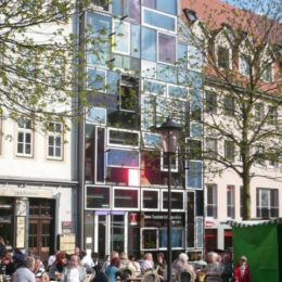 Die Hologrammfassade in Jena bei Sonnenschein. Davor sitzen viele Menschen auf Stühlen um Tische herum.