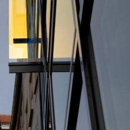 Die Hologrammfassade in Jena in Detail. Das Bild zeigt einen Bereich mit gelben dirchroitischem Glas.
