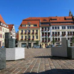 Sitzmöbelunikate aus hellem und dunklen Granit auf dem Obermarkt in Freiberg bei Sonnenschein.