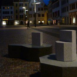 Sitzmöbelunikate aus Granit auf dem Obermarkt am Abend.