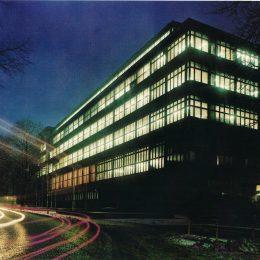 Eine historische Aufnahme des Spinnereimaschinenbaus in der Nacht. Licht strömt von innen nach außen durch die Fenster.