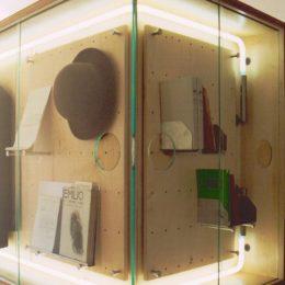 Eine Ausstellungsvitrine im Erich Kästner Museum. Sie ist von innen beleuchtet und enthält einen Hut und meherer Bücher.