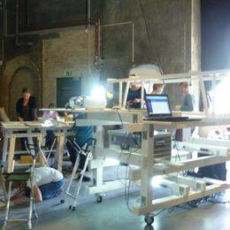Eine Schulklasse erarbeitet Inhalte im Museumslabor in Dresden. Die Schüler sind um eine hölzerne Skulptur verteilt.