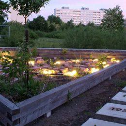 Ein Teil des Plattenbaumuseums in Dresden mit einem beleuchteten Feld aus Ziegelsplitt und großen Betonplatten mit Jahreszahlen auf dem Boden.