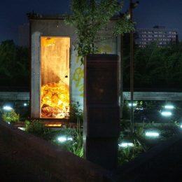 Ein Bereich des Plattenbaumuseums in Dresden bei Nacht. Eine Tür und das Feld davor sind beleuchtet.