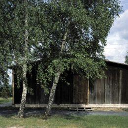 Eine hölzerne Baracke in Ehrenhain Zeithain. Die Baracke steht hinter einer großen Weide.