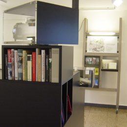 Ein kleiner Raum mit einem Beamer, Büchern und Regalen als Teile einer Ausstellung in der Gedenkstätte Ehrenhain Zeithain.